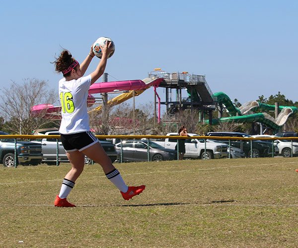 Athlete girl making a soccer ball kick